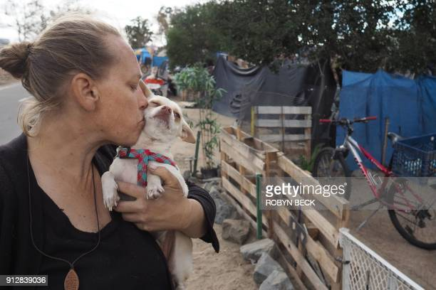 Homeless encampment resident Tammy Schuler kisses one of her pet dogs beside a row of tents and tarps that line the Santa Ana River bicycle path near...