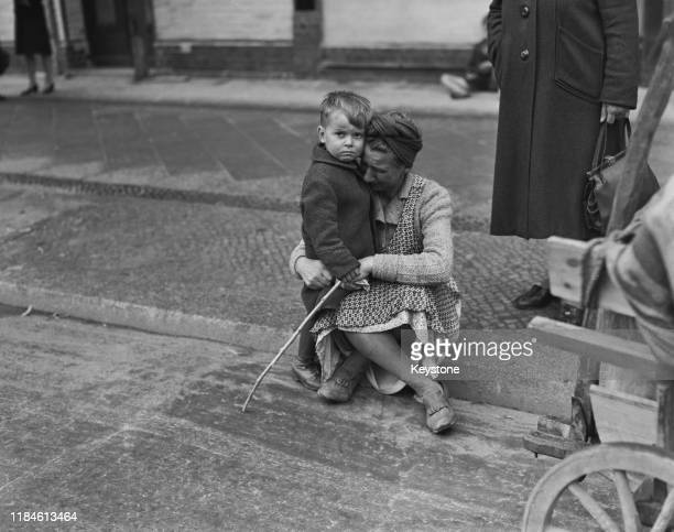 A homeless German refugee tries to console her son amidst the the destruction of post war Germany Berlin June 1945