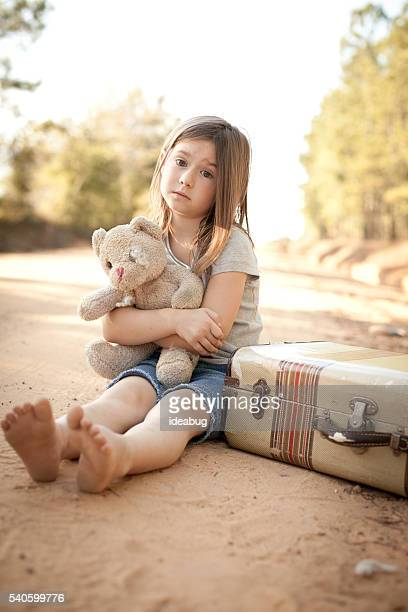 Homeless Girl Hugging Teddy Bear by Suitcase on Dirt Road