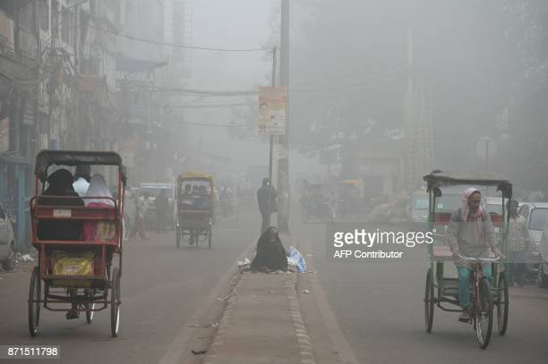 TOPSHOT A homeless Indian resident sits on a road median amid heavy smog in New Delhi on November 8 2017 Delhi shut all primary schools on November 8...