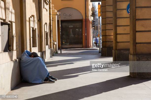 A homeless is sleeping under porches in Bologna during national quarantine in Italy on March 18 2020 in Bologna Italy The Italian government...