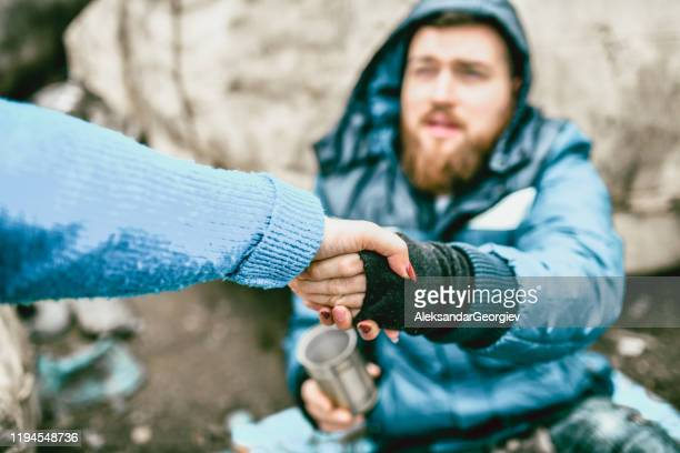 homeless male on the street getting help from female - a helping hand stock pictures, royalty-free photos & images