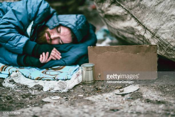 homeless male with sign sleeping near garbage and rags - homelessness stock pictures, royalty-free photos & images