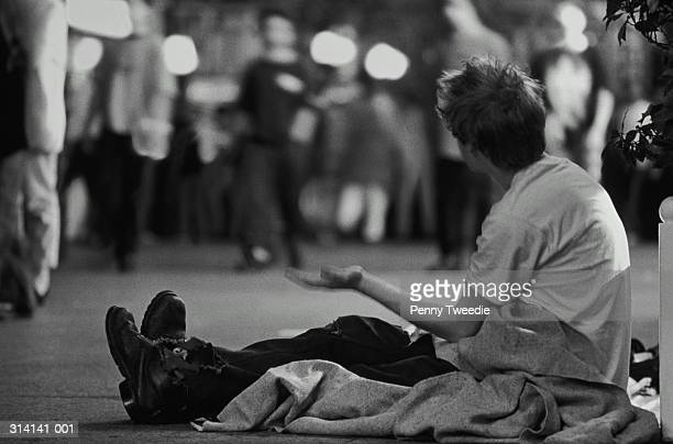 Homeless man begging on street at night (B&W)