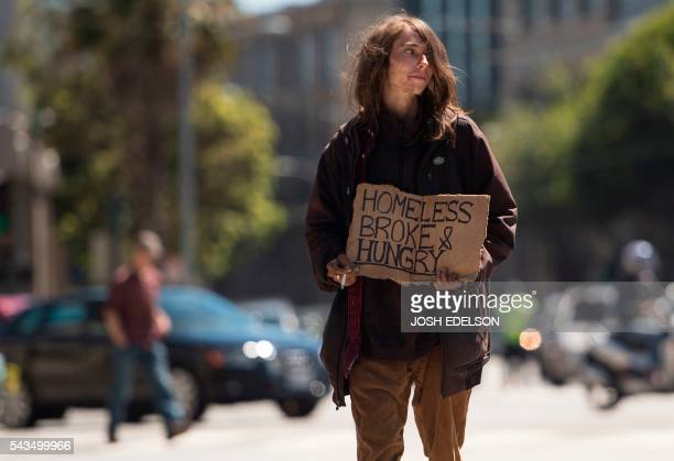 A homeless man begs on a center divider in San Francisco California on June 2016 Homelessness is on the rise in the city irking residents and...