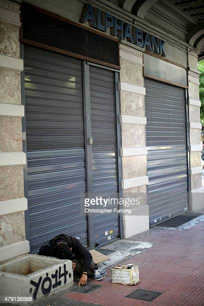 A homeless man begs outside the closed Alpha Bank near Syntagma Square on July 1 2015 in Athens Greece Earlier today Greek Prime Minister Alexis...