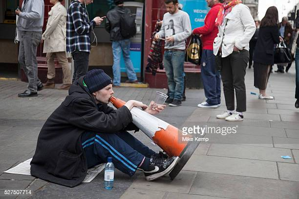 Homeless man busking to make a little money by making music with his voice through a traffic cone on a busy Oxford Street in London amidst the bustle...