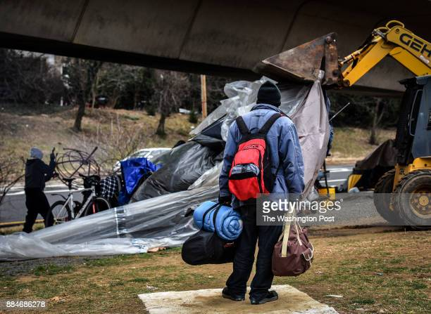 A homeless man carries his possessions as he watches authorities clear out a homeless tent encampment beneath the Whitehurst freeway on February 2017...