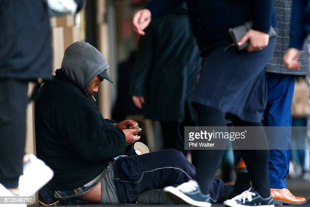 A homeless man counts his paper cup of money in the Auckland CBD on July 13 2017 in Auckland New Zealand Research by Roy Morgan found that economic...