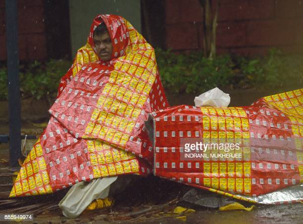 A homeless man covers himself with a plastic sheet during rain from Cyclone Ochki in Mumbai on December 5 2017 Cyclone Ockhi has left 13 people dead...