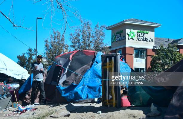 A homeless man eats breakfast outside his tent next to an Extended Stay America hotel near the Santa Ana River in Anaheim California on February 20...