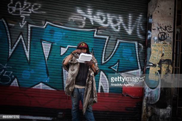 A homeless man eats his food distributed by volunteers in Bogota Colombia on December 15 2017 Homeless people eat their meal distributed by...