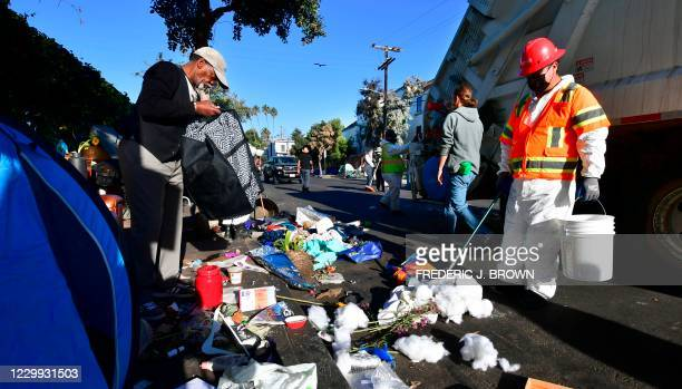 Homeless man goes through his belongings before items on the street are swept away during a cleaning of the street on December 3, 2020 in Venice,...