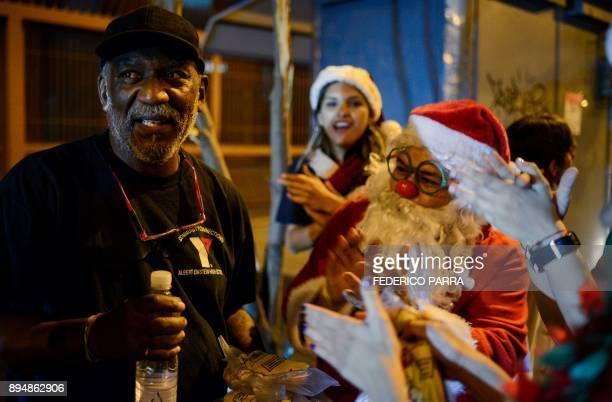 A homeless man greets a volunteer dressed as Santa Claus during the event 'Santa en las calles' in Caracas on December 16 2017 Santa in the Streets...