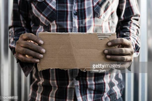homeless man holding cardboard sign - unemployment stock photos and pictures