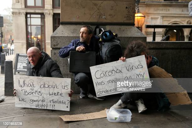 A homeless man holds a sign reading What about us Boris were we gunna isolate Help relating to the UK government's advice to selfisolate if a person...