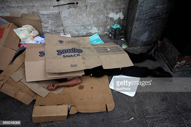 Homeless man in Athens city center sleeping under card boxes on Jun 29 2015