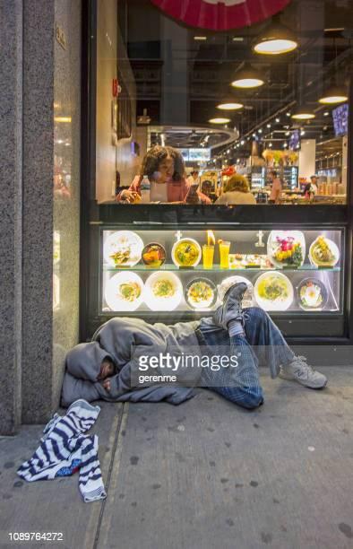 obdachloser vor einem restaurant - kapitalismus stock-fotos und bilder