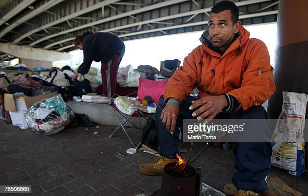 Homeless man Justin Manuel warms his hands with a small fire underneath Interstate 10 where over 100 homeless people sleep each night December 16...