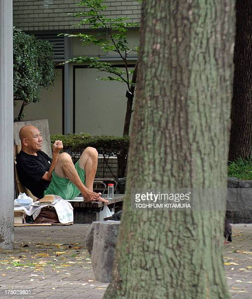 Homeless man kills time while sitting in a park in central Tokyo on July 30, 2013. Japan's jobless rate fell to 3.9 percent in June, dropping to the...