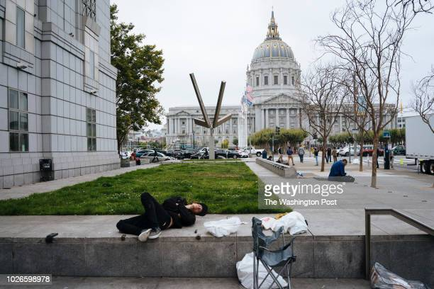 A homeless man lies motionless on the steps of the San Francisco Public Library in San Francisco California on August 22 2018