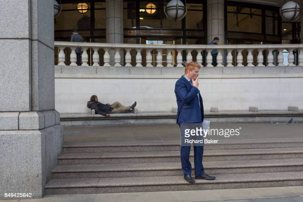 Homeless man lies on City seating as a businessmen smokes, on 14th September 2017, in the City of London, England.