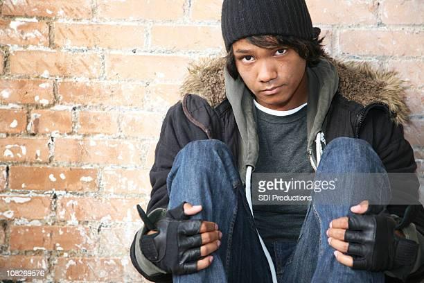 Homeless Man Looking Ahead Against a Brick Wall