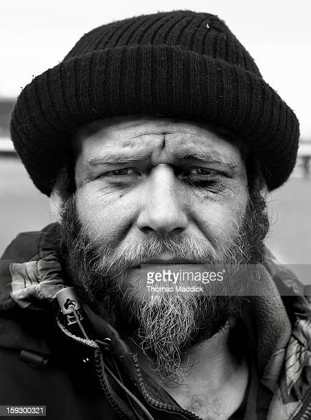 Homeless man looks thoughtfully into the lens on the beach in Skegness England. Dr Geebers as he calls himself has been traveling the UK coast making...