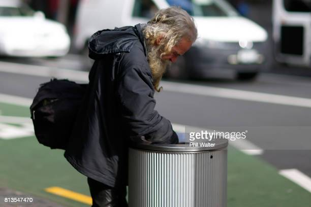 A homeless man looks through a rubbish bin in the Auckland CBD on July 13 2017 in Auckland New Zealand Research by Roy Morgan found that economic...
