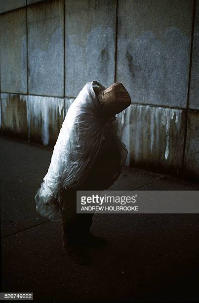 A homeless man on the streets of New York tries to keep warm by wrapping himself in plastic on a zero degree winter day