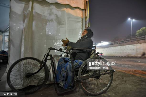A homeless man outside a temporary shelter home at Nizamuddin Basti on December 18 2018 in New Delhi India There are some 83 permanent shelters and...