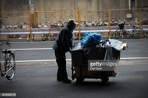 A homeless man pushes a cart with his belongings in the slum area of Kamagasaki on April 23 2016 in Osaka Japan Kamagasaki a district in Japan's...