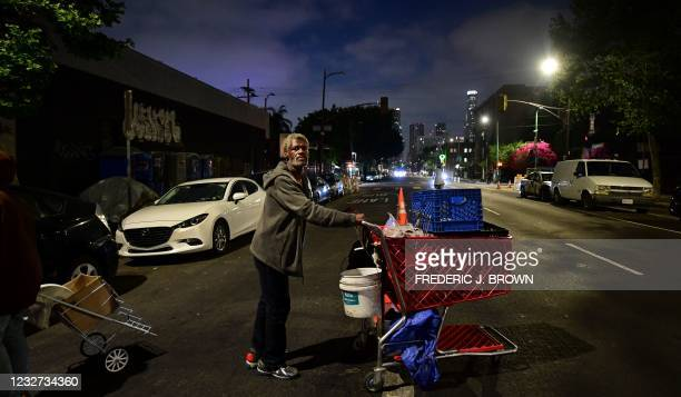 Homeless man pushes his cart of belongings along the streets of downtown Los Angeles, California on May 6, 2021 where activists, joined by...