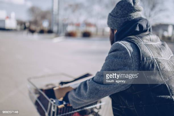homeless man pushing shopping cart - homeless person stock pictures, royalty-free photos & images