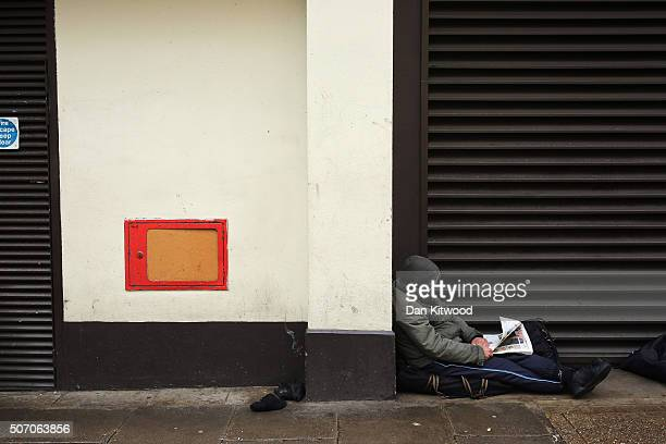A homeless man reads a newspaper near Trafalgar Square on January 27 2016 in London England A group of 21 charities including Crisis St Mungos and...