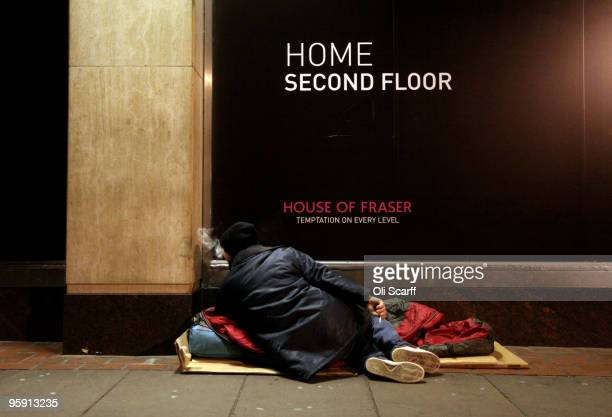 A homeless man rests on his sleeping bag in the street next to a department store after receiving food and a hot drink from the homelessness charity...