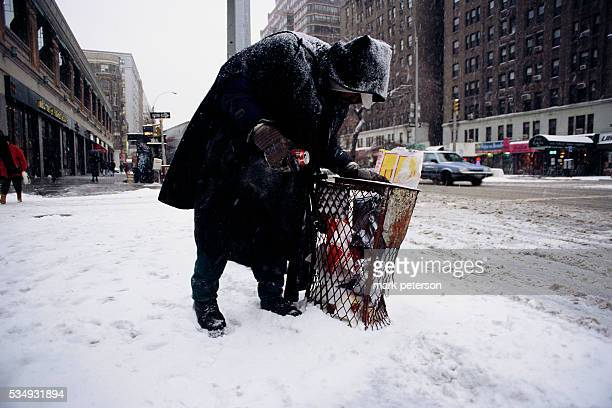 A homeless man searches through a garbage can on the side of a New York street