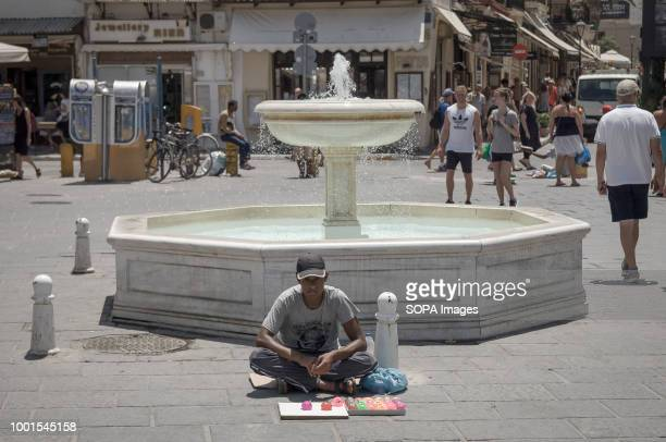 A homeless man seen sitting next to a fountain at the old port of Chania Chania is a very touristic place in Crete where tourists come to enjoy the...