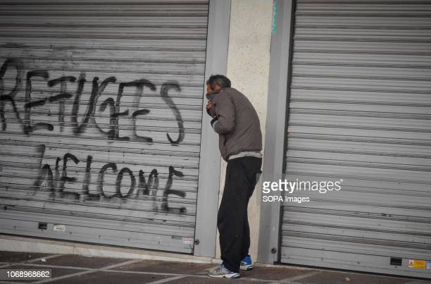 A homeless man seen trying to take a cover during the protest Protest to mark the 10th Anniversary of Alexis Grigoropoulos he was shot fatally by a...