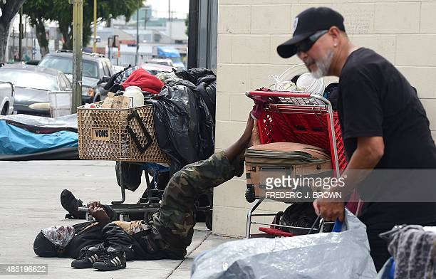 A homeless man sets up his tent as a homeless woman nearby checks her cellphone while resting her feet on a cart full of belongings in Los Angeles...