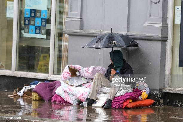 Homeless man shelters from the rain underneath an umbrella in London.