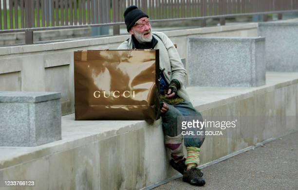 Homeless man sits beside a Gucci shopping bag in central London, 15 November 2007. AFP PHOTO/CARL DE SOUZA