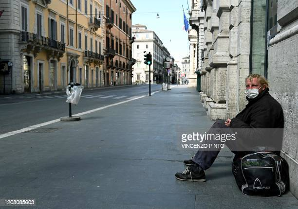 TOPSHOT A homeless man sits in a deserted Via del Corso main street in central Rome on March 24 2020 during the country's lockdown aimed at stopping...