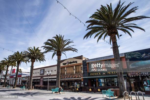 A homeless man sits in front of closed bars and restaurants in Hermosa Beach California on March 28 2020 Los Angeles County closed all beaches today...