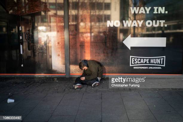 A homeless man sits in the street as shoppers make their last minute purchases on Christmas Eve on December 24 2018 in Birmingham England Financial...