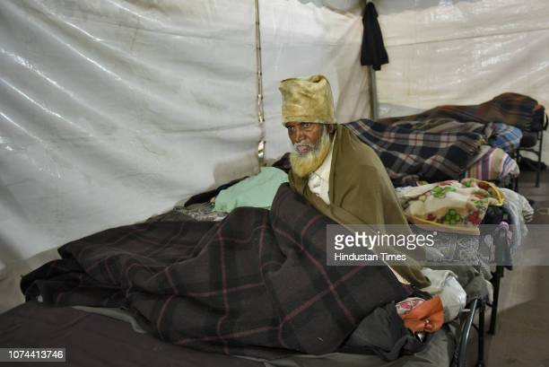 A homeless man sits on a bed inside a temporary shelter home at Nizamuddin Basti on December 18 2018 in New Delhi India There are some 83 permanent...