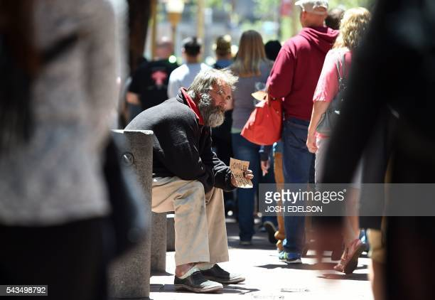 A homeless man sits on a chain while people wait to board a trolly car in downtown San Francisco California on Tuesday June 2016 The man sat down...
