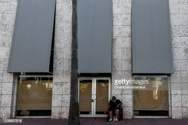 Homeless man sits on a wheel chair outside of a closed shop in South Beach, Miami, amid fears over the spread of the novel coronavirus on April 1,...