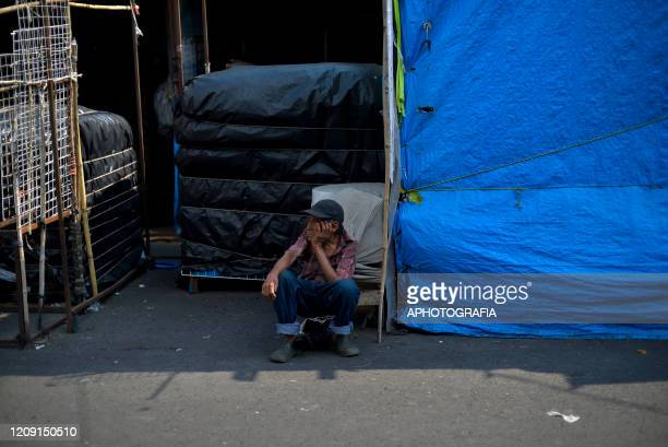 A homeless man sits on the street where he will live through the COVID19 crisis on April 3 2020 in San Salvador El Salvador On March 21st President...