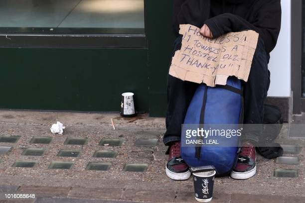 A homeless man sits with a handwritten sign collecting money from passersby in central London on August 13 2018